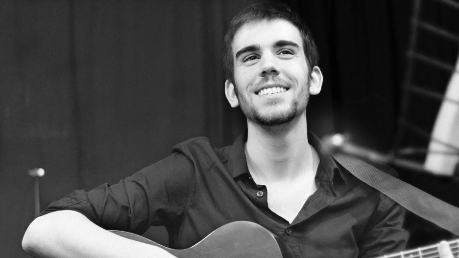 Baptiste Chevreau holding his guitar, smiling
