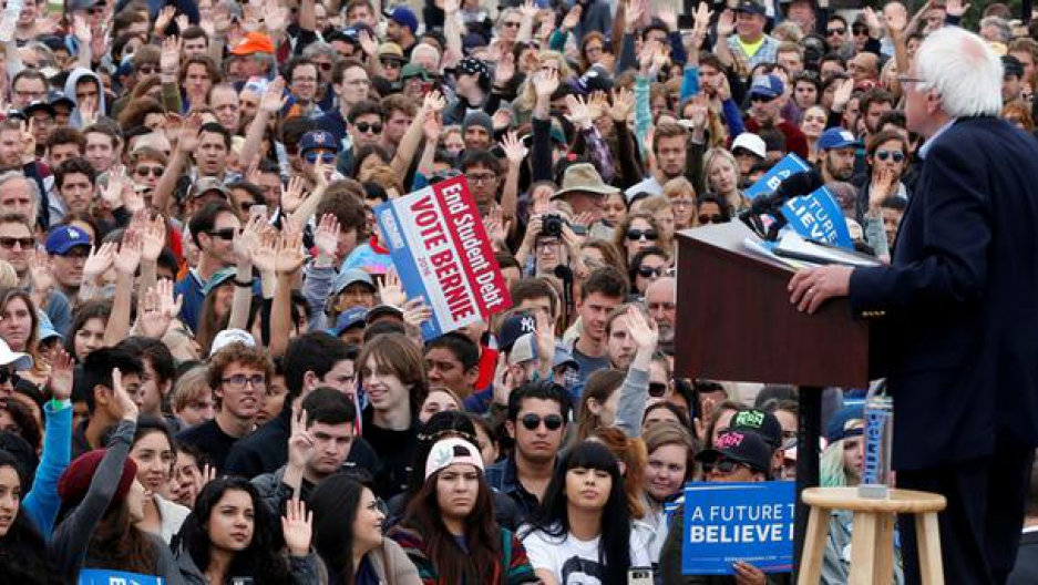 Democratic presidential candidate Bernie Sanders faces a very large crowd of young people who hold their hands up in the air after he asks who among them has student loans.