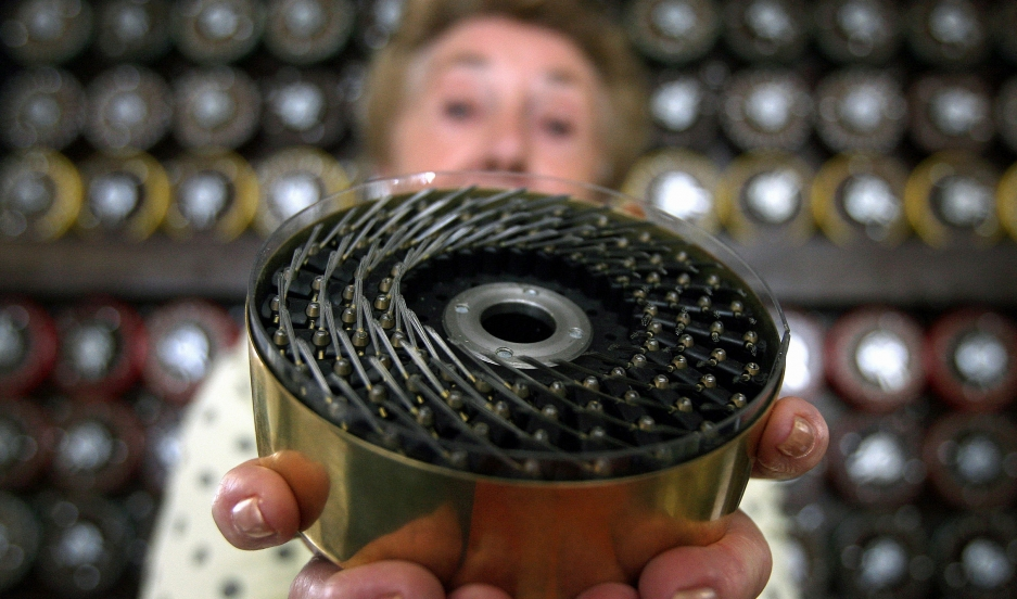 Former Bombe operator Jean Valentine shows a drum of British Turing Bombe machine in Bletchley Park Museum in Bletchley, central England, September 6, 2006. For the first time in sixty years Bletchley Park re-created the way the 'unbreakable' Enigma code