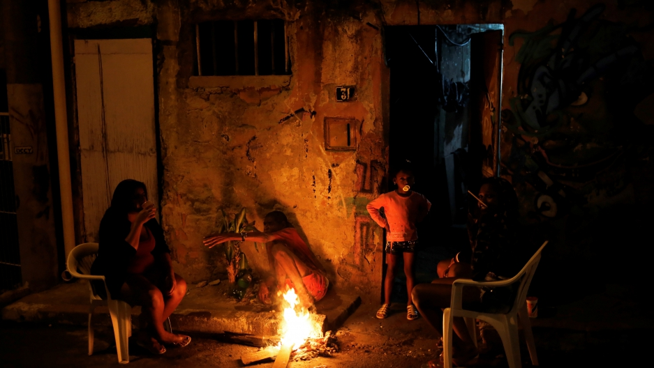 A family is pictured at the entrance of their house at a slum, or favela, in Rio de Janeiro