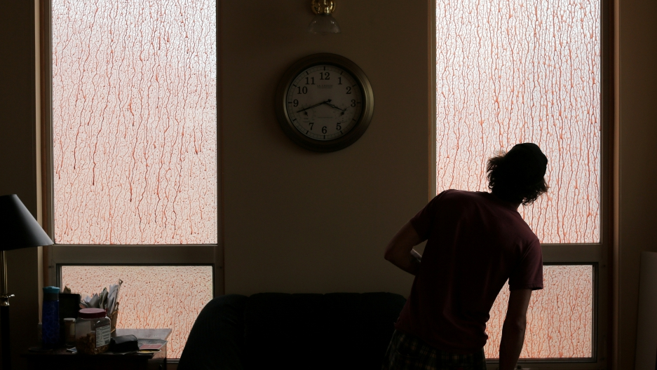 Wes Gerwien, 28, looks out a window of his family home
