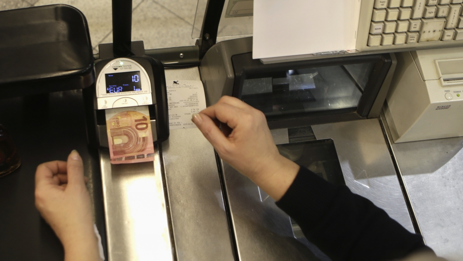 A cashier inspects a euro banknote at a shop in Vilnius January 1, 2015. (Ints Kalnins/Reuters)