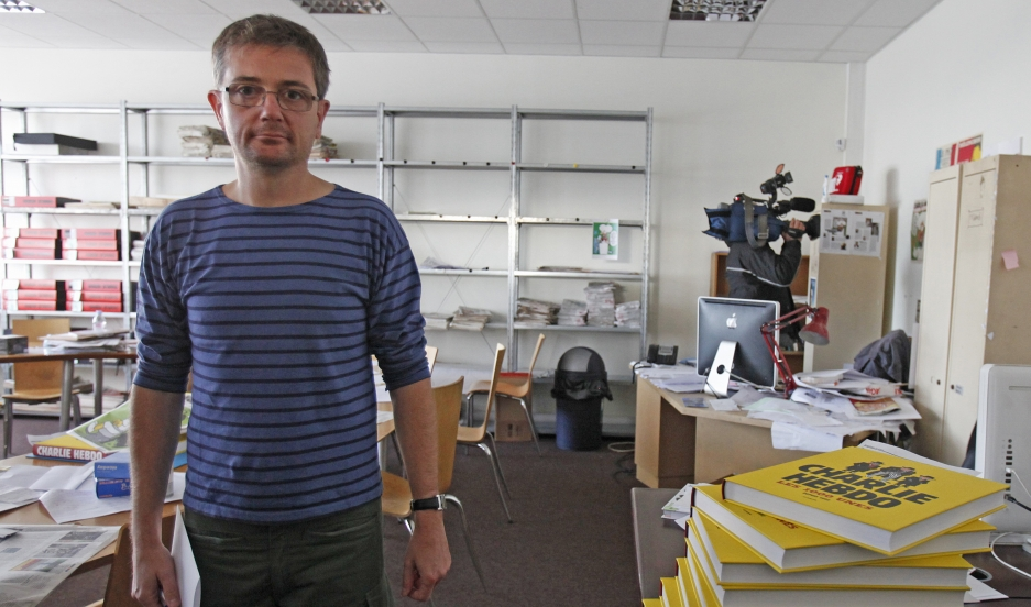French cartoonist Charb, publishing director of French satirical weekly Charlie Hebdo, poses for photographs at their offices in Paris, September 19, 2012. Charlie Hebdo published cartoons of the Prophet Mohammad on Wednesday, a decision criticised by the
