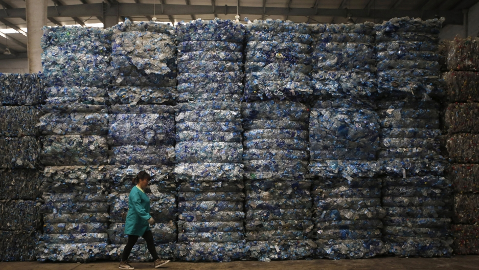 A worker walks past piles of plastic PET bottles at Asia's largest PET plastic recycling factory