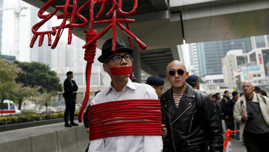 "An artist ties himself with a rope that spells out ""Kidnap"" during a protest over the disappearance of booksellers in Hong Kong, Jan. 10, 2016."