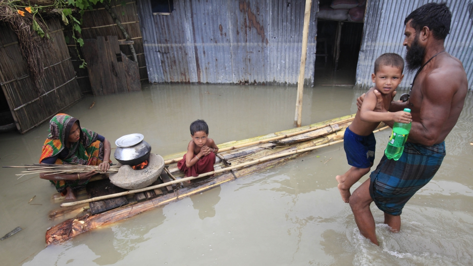 A woman cooks next to her child on a makeshift banana plant raft at a flooded village in Bangladesh July 3, 2012. Low-lying Bangladesh is perhaps the most vulnerable nation to the impacts of climate change.