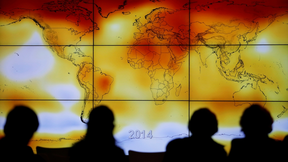 Participants are seen in silhouette as they look at a screen showing a world map with climate anomalies during the World Climate Change Conference 2015