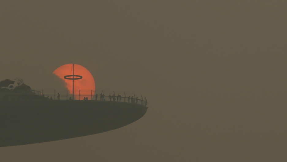 People watch the sun set through the pollution