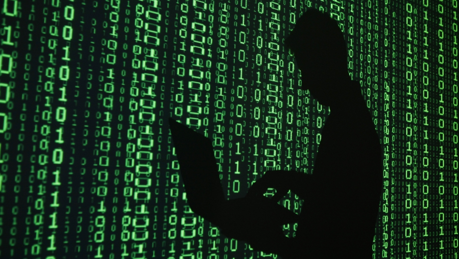 An illustration shows a projection of binary code around the shadow of a man holding a laptop computer in an office in Warsaw June 24, 2013.