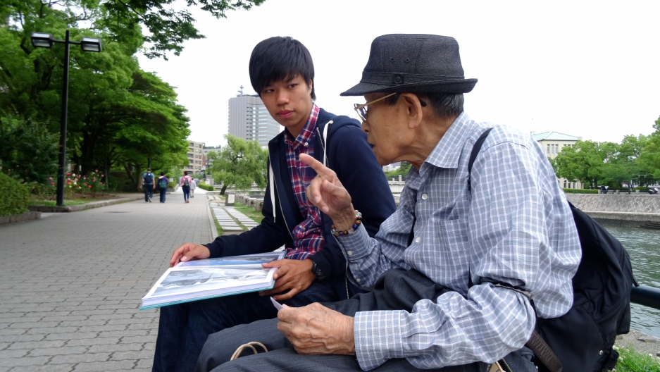 Masaaki Murakami, a volunteer guide at Hiroshima's Peace Memorial Park listens to 87-year-old atomic bomb survivor Noriho Azuma.