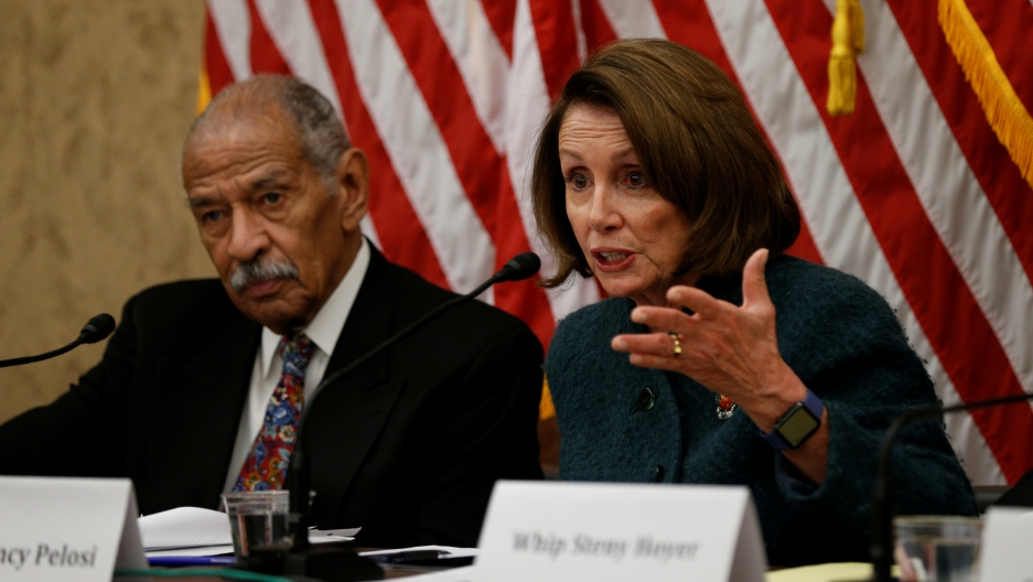 House Minority Leader Nancy Pelosi and Representative John Conyers sit side by side on a panel about Trump's visa ban on February 2, 2017.