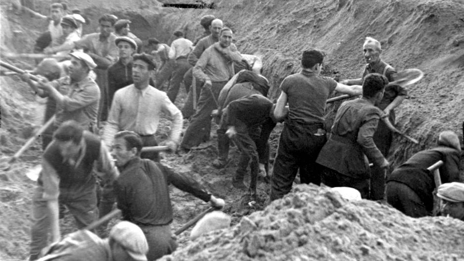 Jews digging a trench in Ponar forest, in which they were later buried, after being shot