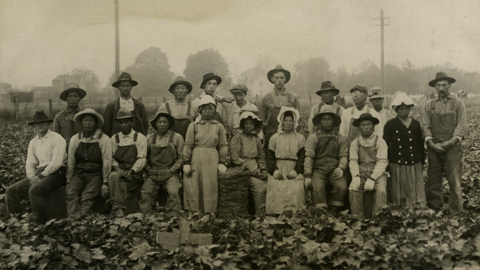 A group of workers pose in a farm, wearing their work clothes. Top row standing, bottom row sitting. Black and white photo.
