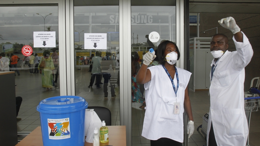 Health workers wearing protective masks and gloves gesture as they talk at the Felix Houphouet Boigny international airport in Abidjan August 12, 2014.