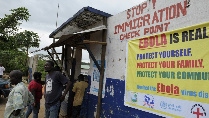 Liberian soldiers check people for Ebola