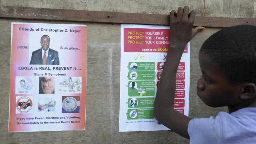 A boy looks at posters issued by the Liberian government warning against Ebola at Duwala market in Monrovia.