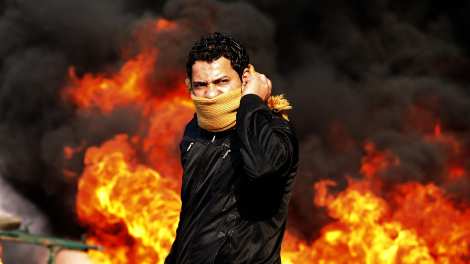 A protester stands in front of a burning barricade during a demonstration in Cairo January 28, 2011.