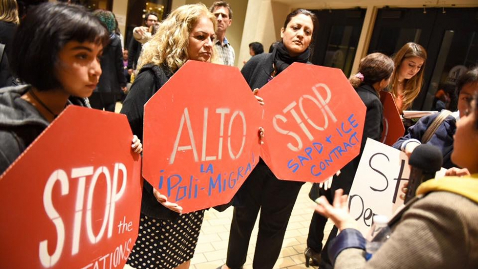 Protestors hold up signs in the shape of stop signs and call for the end of immigration detentions