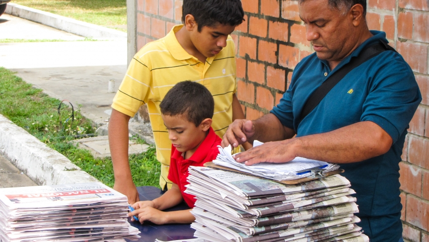 Jose Luis Farrera (with his sons) runs a newsstand in Venezuela. But business is down, because he can't get enough newspapers.