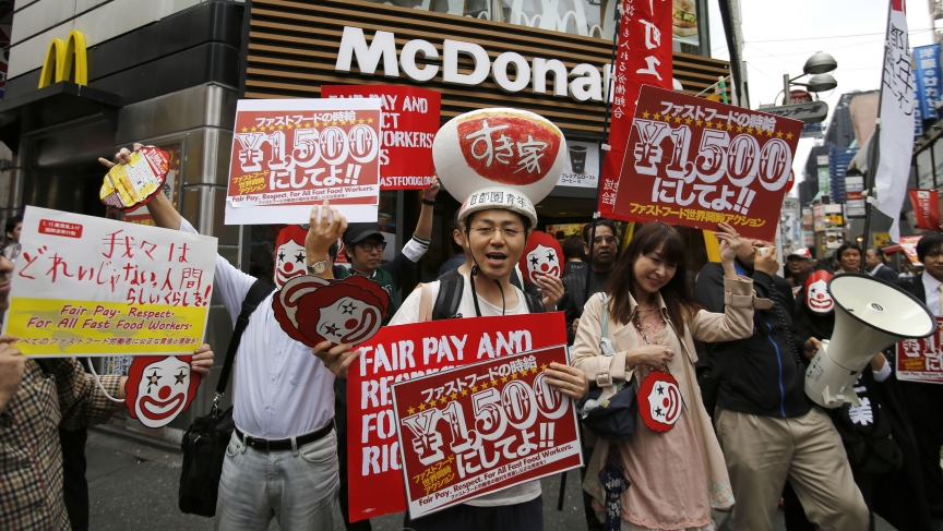 Demonstrators holding posters march during a protest to demand higher wages for fast-food workers in front of a McDonald's fast-food restaurant in Tokyo's Shibuya shopping and amusement district May 15, 2014.