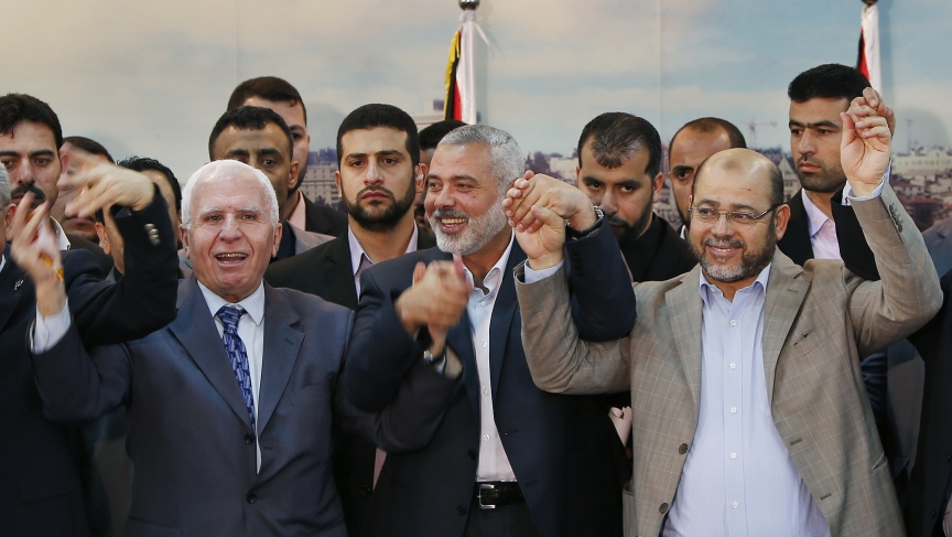 Senior Fatah official Azzam Al-Ahmed, left, head of the Hamas government Ismail Haniyeh, center, and senior Hamas leader Moussa Abu Marzouq announce a reconciliation agreement in Gaza City April 23, 2014.