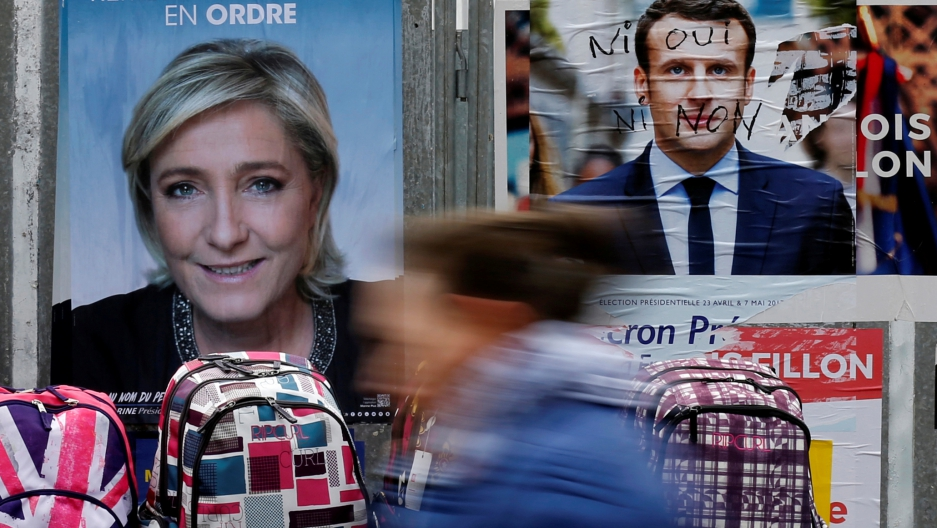 A woman walks past official posters of candidates for the 2017 French presidential election Marine Le Pen and Emmanuel Macron