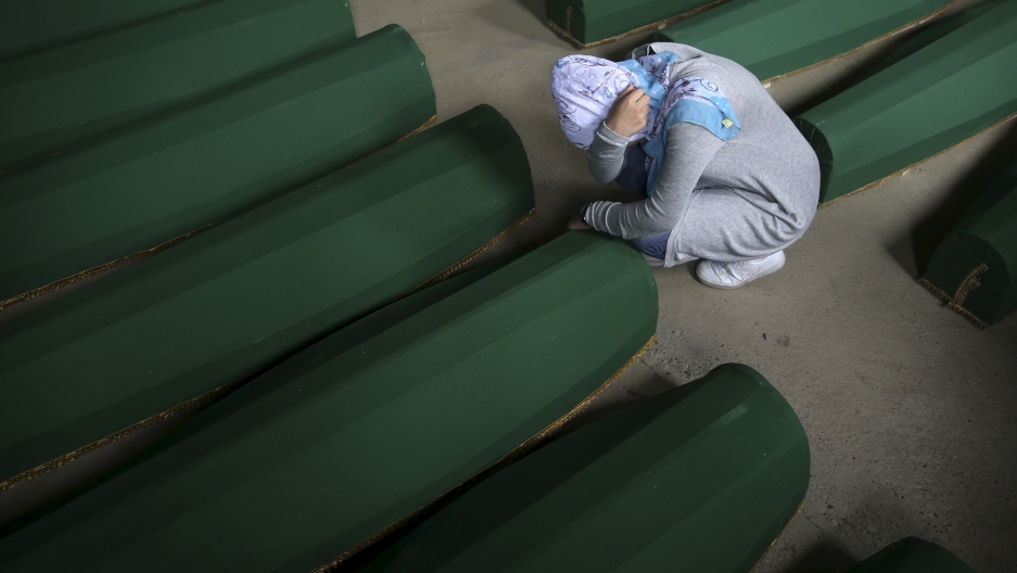 A Muslim woman cries near the coffin of her relative