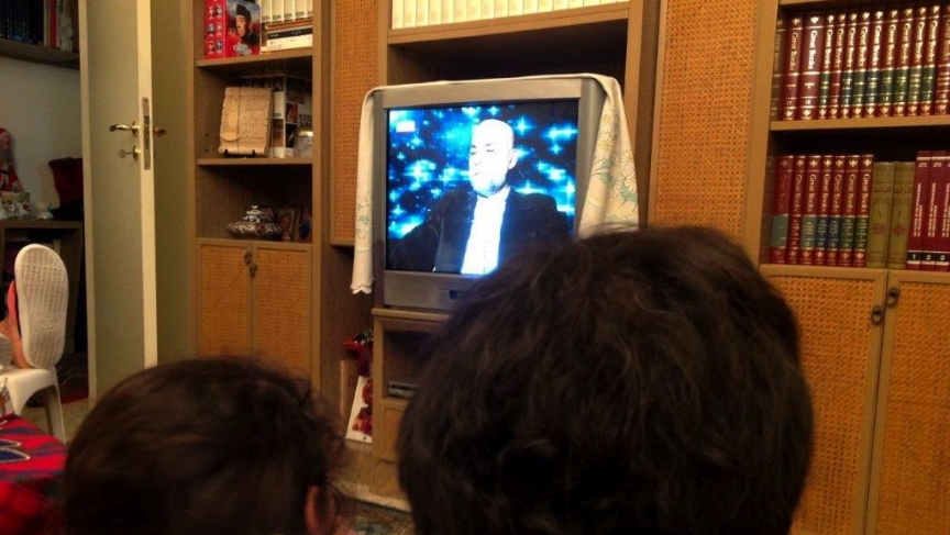 A Lebanese family watches TV fortune teller Mike Feghaly give his predictions for 2014