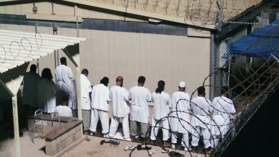 Detainees participate in an early morning prayer session at Camp IV at the detention facility in Guantanamo Bay