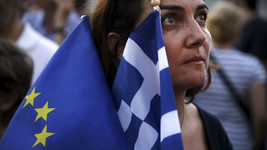 A pro-Euro protester holds a European Union and a Greek national flag during a rally in front of the parliament building in Athens, Greece, July 9, 2015.