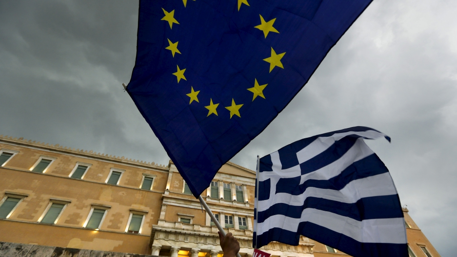 Two flags - one for Greece and one for the EU - fly during protests in Athens this week