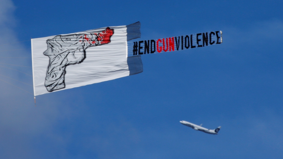"A plane pulls a banner that reads ""#End Gun Violence"" over a vigil for the Pulse night club victims"