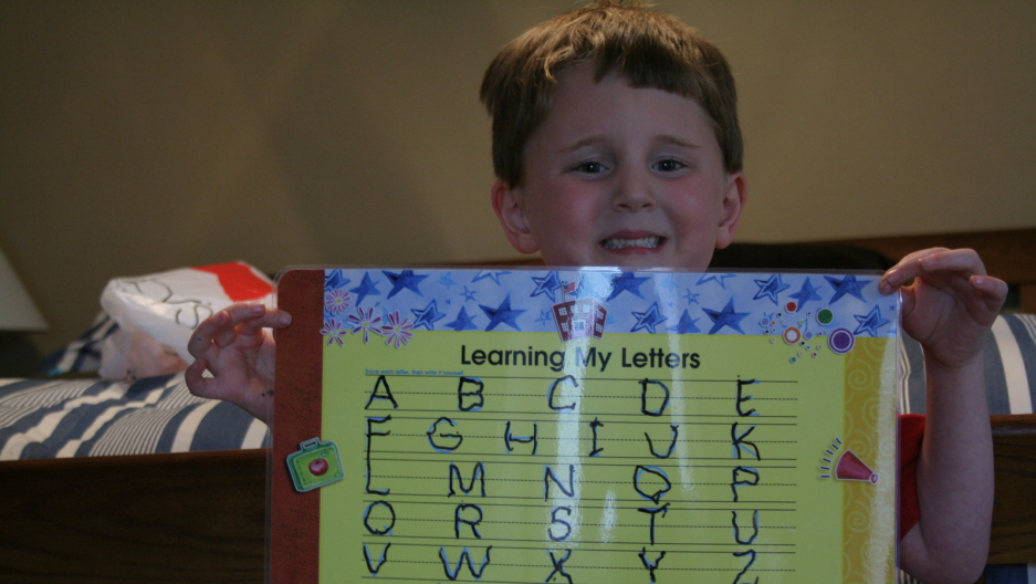 a boy shows off his handwriting practice