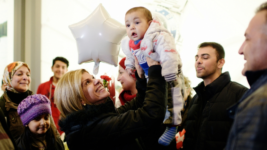 Tima Kurdi (middle), holds up her nephew Sherwan Kurdi as she welcomes her brother Mohammed Kurdi (R), and his family at Vancouver International airport in Vancouver, British Columbia, December 28, 2015.