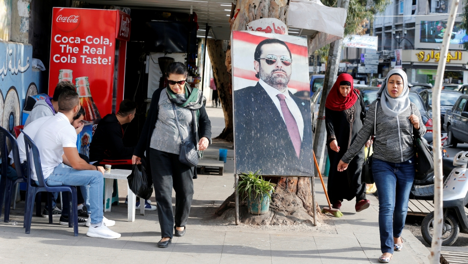 People walk next to a poster depicting Lebanon's Prime Minister Saad al-Hariri