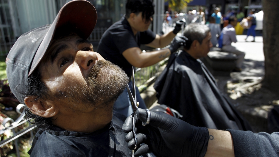 "A volunteer from the social work community ""Friends of the World"" trims the beard of a homeless man in San Jose, Costa Rica February 24, 2016."