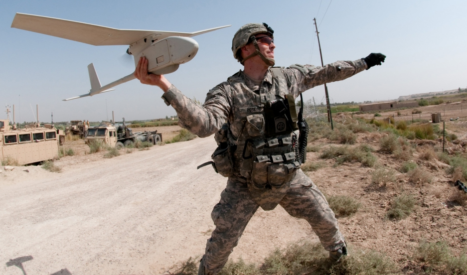 Army 1st Lt. Steven Rose launches an RQ-11 Raven unmanned aerial vehicle near a highway bridge project along the Euphrates River north of Taqqadum, Iraq.