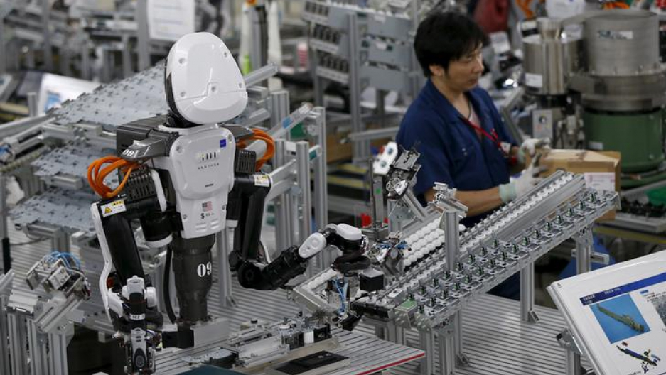 A robot with human-like features works on an assembly line beside a human worker at a factory of Glory Ltd., a manufacturer of automatic change dispensers, in Kazo, north of Tokyo, Japan, July 1, 2015.