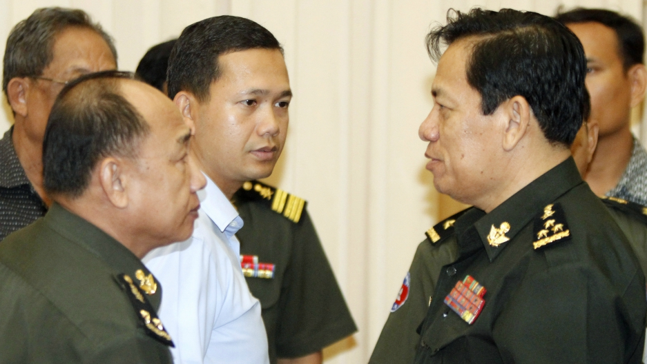 Hun Manet (C), son of Cambodia's Prime Minister Hun Sen, looks at Cambodia's Defense Ministry spokesman Chhum Socheat (R), after a news conference at the Council of Ministers in Phnom Penh April 22, 2011