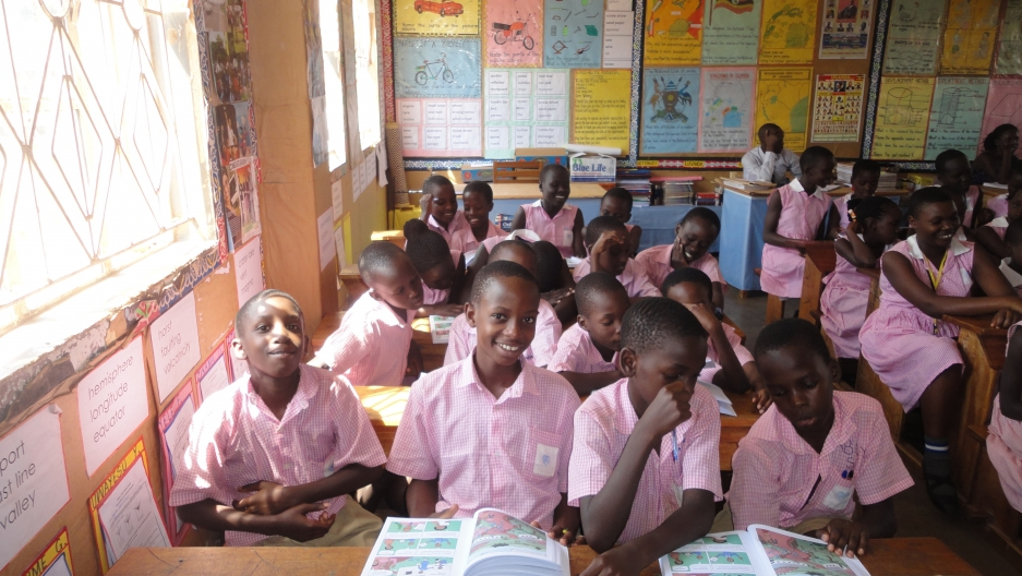 Students use  the final version of a children's book to teach kids how to identify false health claims in a classroom in Uganda.