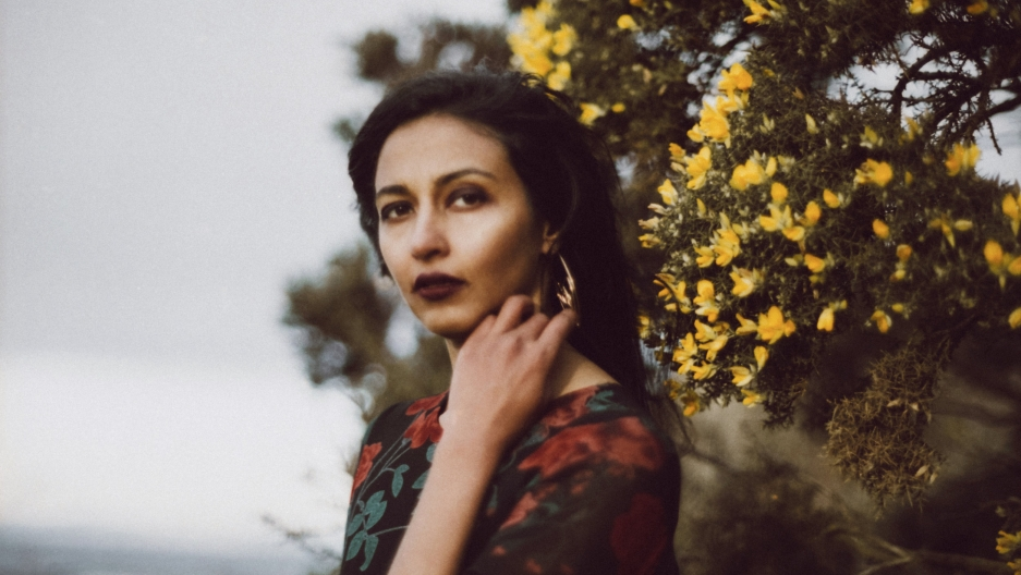 Artist Lakshmi Ramgopal poses in front of yellow flowers in this 2017 photograph.