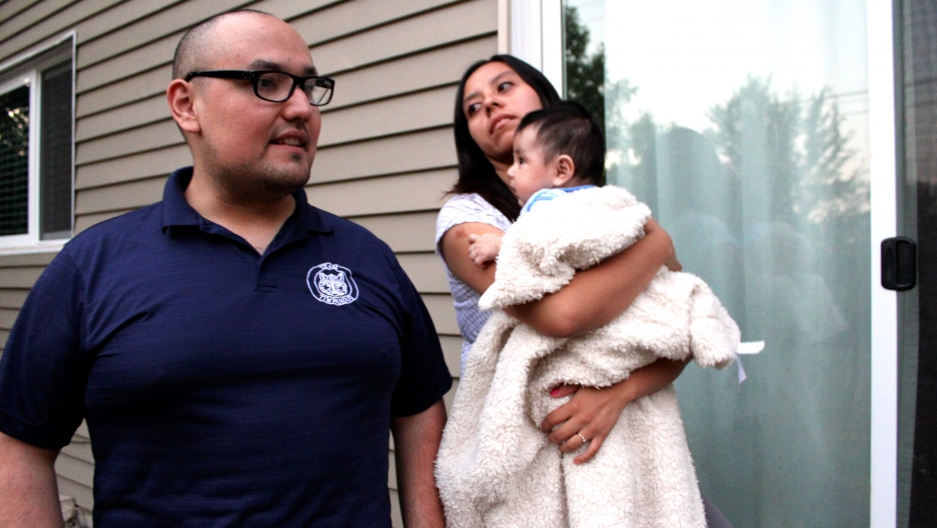 Man and woman with baby in front of house