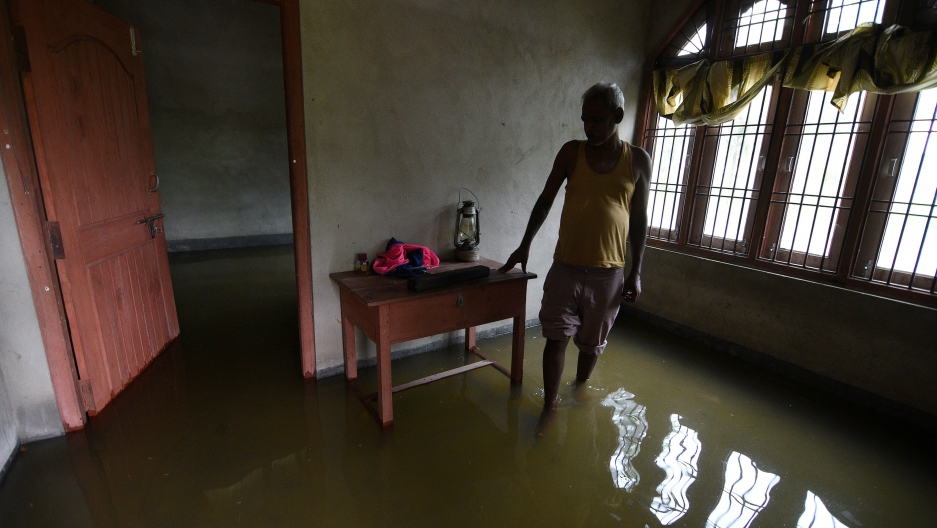 A man stands inside his partially submerged house