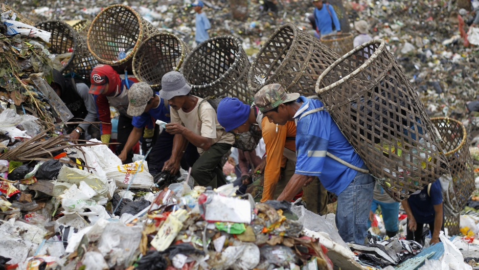 Scavengers search for items to recycle at a waste dump in Bogor, a city in Indonesia's West Java province, on June 3, 2013.
