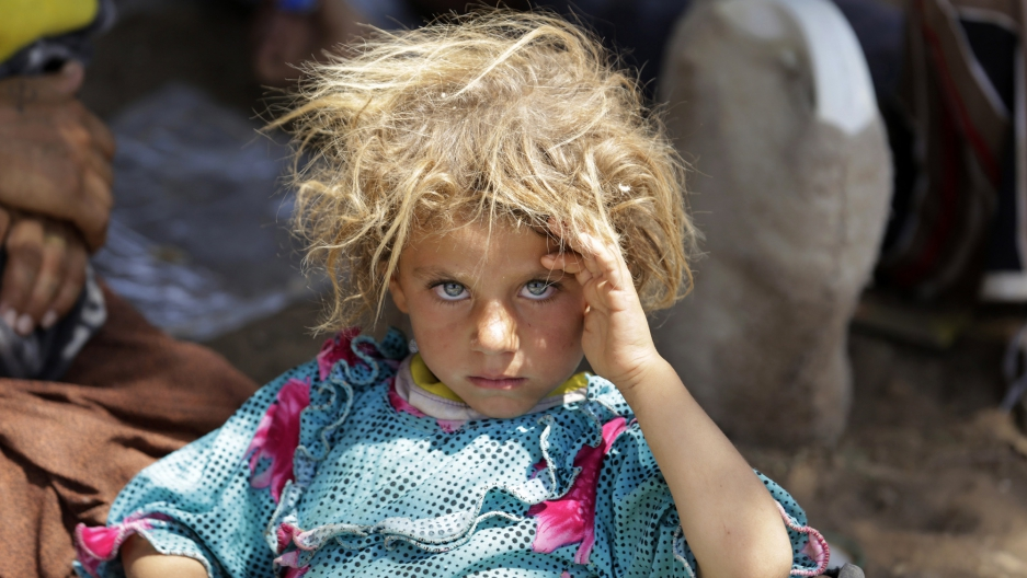An Iraqi girl from the minority Yazidi sect, after fleeing violence in Sinjar, rests at the Iraqi-Syrian border crossing in Fishkhabour on Aug. 13, 2014.