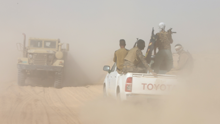 Iraqi army personnel ride on military vehicles