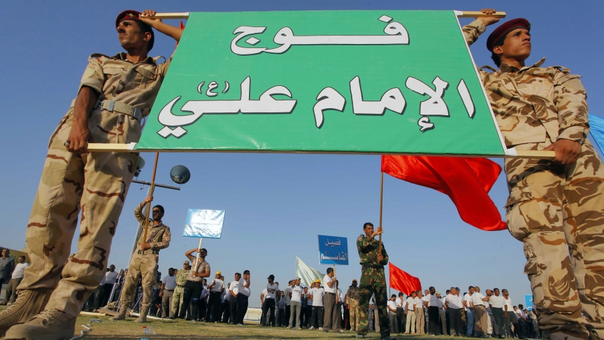 Shi'ite volunteers, who have joined the Iraqi army to fight against the predominantly Sunni militants from the radical Islamic State of Iraq and Syria (ISIS), hold a sign during a graduation ceremony after completing their field training in Najaf, that re