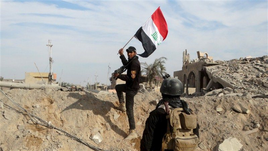 A member of the Iraqi security forces holds an Iraqi flag in the city of Ramadi.