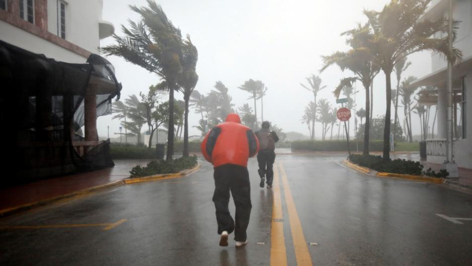 People walk along a street in South Beach as Hurricane Irma arrives
