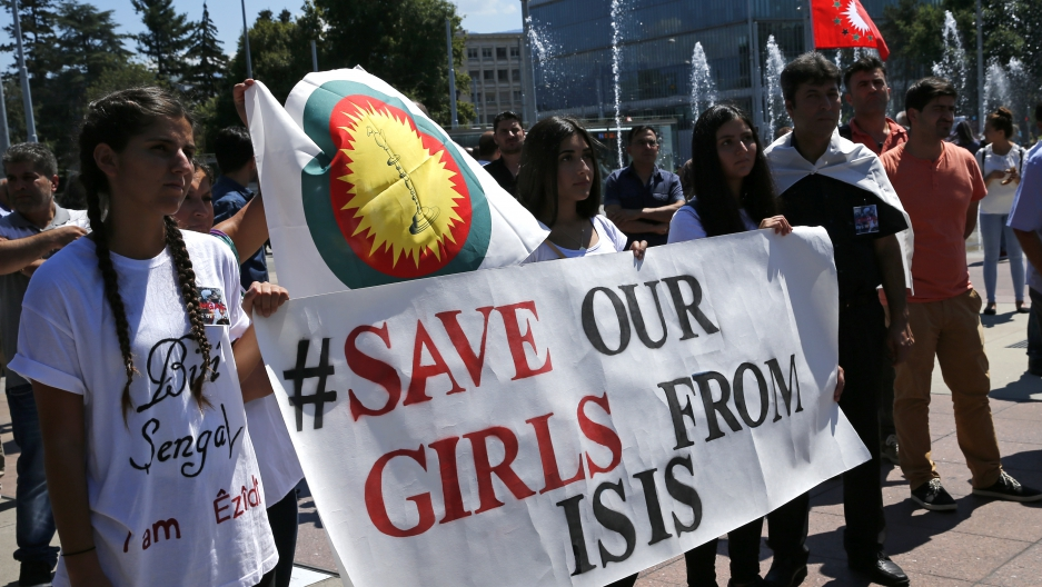 Women hold a banner during a demonstration marking the first anniversary of  ISIS' surge on Yazidis of the town of Sinjar, in front of the United  Nations ...